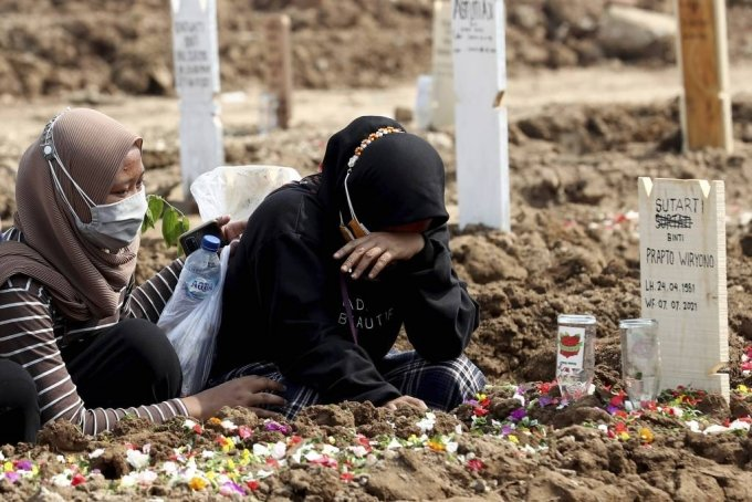 지난 7월(현지시간) 인도네시아 자카르타의 한 공동묘지에서 한 여성이 코로나19로 숨진 친지의 묘지 앞에 앉아 흐느끼고 있다./AP=뉴시스