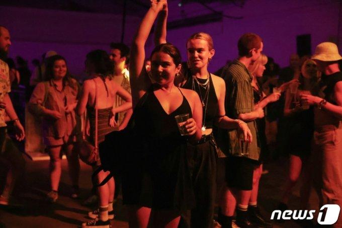 7월 19일(현지시간) 영국 런던에서 자정이 넘어 코로나 방역 조치가 해제되자 이를 즐기려는 사람들이 모여 춤을 추고 있다.  /로이터=뉴스1