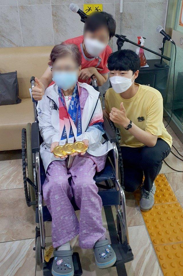 2020도쿄올림픽 양궁 '3관왕'을 거머쥔 안산 선수가 지난 2일 오후 광주 모 병원에 입원한 외할머니 목에 금메달을 걸은 뒤 함께 인증사진을 찍고있다./사진=뉴시스(독자제공)