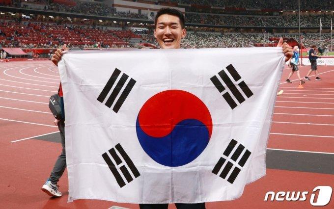 육상 국가대표 우상혁 선수가 지난 1일 오후 도쿄 올림픽스타디움에서 열린 2020 도쿄올림픽 남자 높이뛰기 결승전 경기를 마친 후 태극기를 들고 기뻐하고 있다./사진=뉴스1