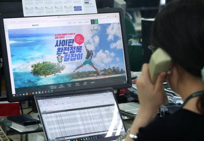 지난달 서울 중구 모두투어 본사에서 직원들이 곧 재개될 사이판 여행 상품을 보며 단체여행 예약 목록을 확인하는 모습. /사진=뉴시스