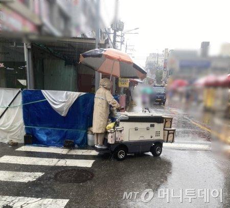 전동 카트에 큰 우산을 꽂아 다니던, 요구르트를 배달하시는 여사님. 그나마 이렇게라도 비를 피할 수 있어 다행이라 여겼다./사진=남형도 기자