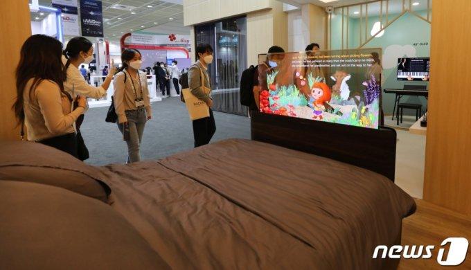 지난 8월25일 서울 코엑스에서 열린 IMID 2021(한국디스플레이산업 전시회)에서 관람객들이 스마트침대에 설치된 LG디스플레이 투명 OLED를 둘러보고 있다. /뉴스1