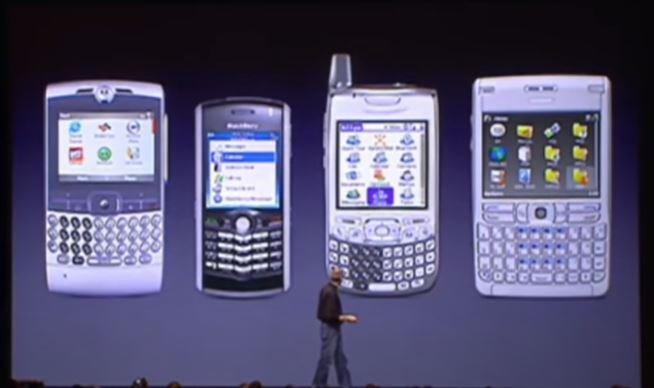 2007년 1월 9일 샌프란시스코 모스코니 컨벤션센터에서 열린 2007년 맥월드 행사에서 스티브 잡스 CEO가 자사의 첫 스마트폰인 '아이폰'을 발표하면서 경쟁사의 재품인  모토롤라Q, 블랙베리, 팜 트레오, 노키아E62 (사진 왼쪽부터)에 대해 문제점을 설명하고 있다./사진제공=애플 발표 동영상 캡쳐
