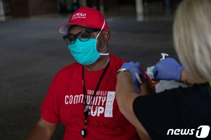 (사우스필드 AFP=뉴스1) 우동명 기자 = 24일 (현지시간) 미시간주 사우스필드에 있는 코로나19 백신 접종소에서 주민이 모더나 백신 부스터샷을 맞고 있다.  (C) AFP=뉴스1