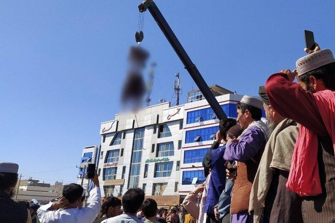 기중기에 매달린 납치범 시신을 보고 있는 아프간 시민들 /사진=AFP
