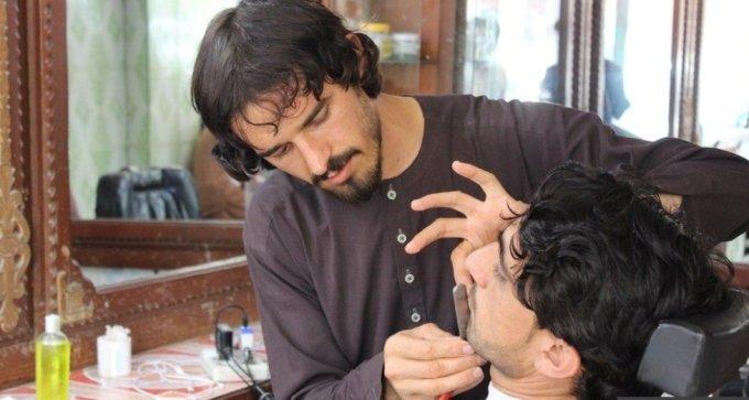 아프가니스탄의 한 이발사가 손님의 수염을 다듬고 있다./BBC 캡처