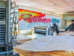 """[사진] """"8차 당 대회 결정 관철"""" 걸린 북한 목재가공공장"""