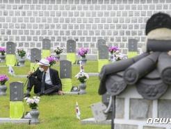 [사진] 아들 묘비 앞에 앉은 아버지