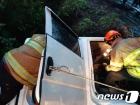 소방당국, 빗길 속 사고난 트럭서 구조작업