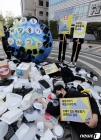배달용 쓰레기에 누운 환경단체 활동가들