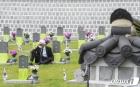 아들 묘비 앞에 앉은 아버지